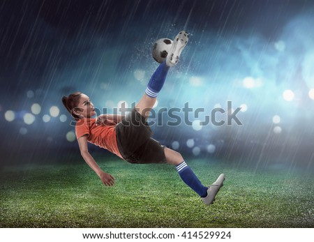 Asian woman football player kick ball on the stadium
