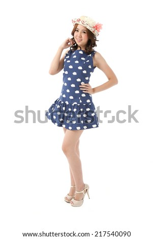 Asian woman full body posing in cloudy print sleeveless dress with flower top hat isolated on white background.