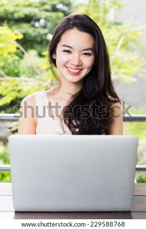 Asian woman happily using a notebook - stock photo