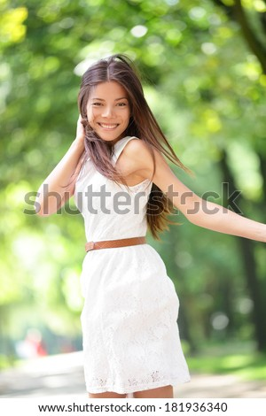 Asian woman happy running in summer / spring city park joyful and smiling in white sundress around trees. Beautiful fresh multiracial Asian Caucasian girl female model in her 20s outside. - stock photo