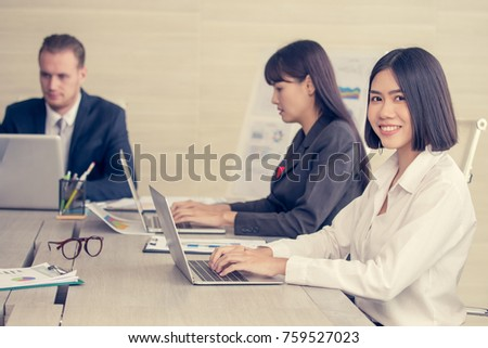 Asian Woman have a meeting with team for Business present. Woman working at meeting room with team. People working concept. Vintage Tone.