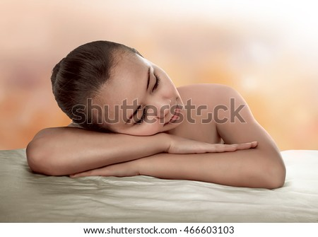Asian woman have relax time. He have natural skin and look relax with orange background