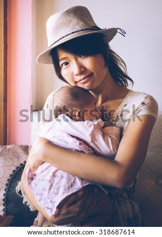 Asian woman hold tight her daughter and see camera. Vintage retro style photo with color filters, vignette effect, and some fine film noise added. - stock photo