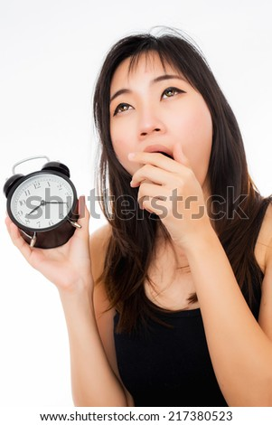 Asian woman holding an alarm clock in the morning