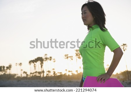 Asian woman holding body board - stock photo