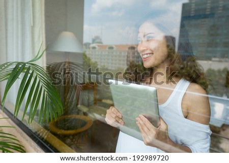Asian woman holding digital tablet while looking through the window - stock photo