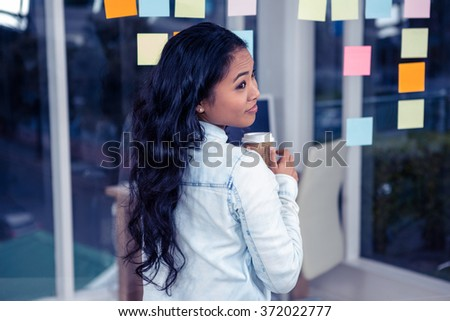 Asian woman holding disposable cup against glass wall