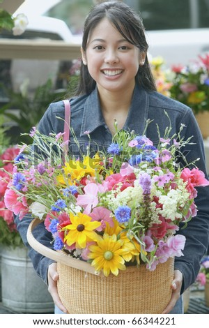Asian woman holding flowers in basket - stock photo