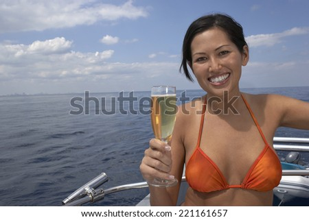 Asian woman holding glass of champagne