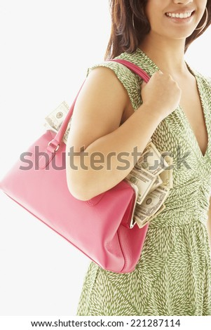 Asian woman holding handbag full of money - stock photo