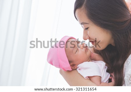 Asian woman holding her sleeping baby girl, close up - stock photo