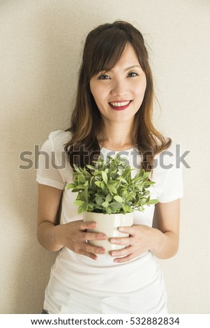 asian woman holding plant