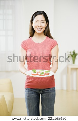 Asian woman holding plate of food - stock photo