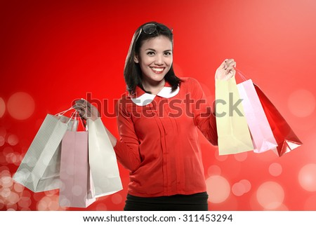 Asian woman holding shopping bag with colorful christmas background - stock photo