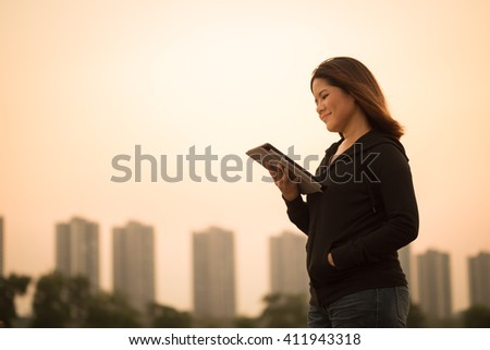 asian woman holding tablet with sunset sky background - stock photo