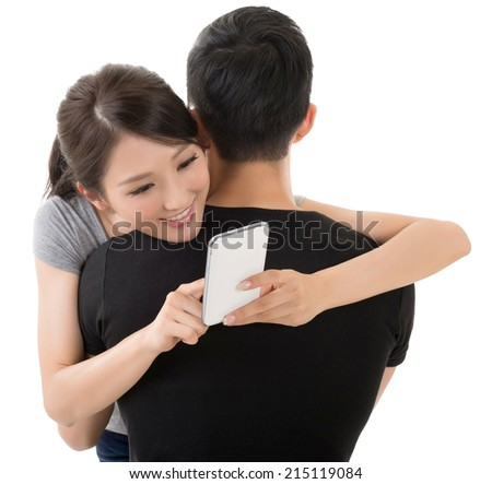 Asian woman hug her boyfriend and use the cellphone. - stock photo
