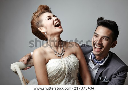 Asian woman in a white bride dress sitting on a chair and Asian man in a white shirt with grey suit in grey background - stock photo