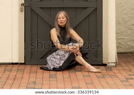 Asian woman in black and white outfit sits by locked door on brick walkway.  Location is rustic Liberty Village, a shopping area in Flemington, New Jersey,
