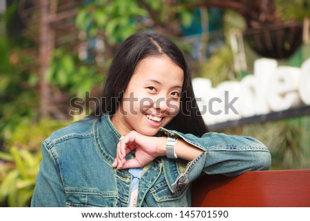 Asian woman in blue jeans shirt smiling