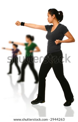 Asian woman in combat stance delivering a right punch with other females in background. Isolated on white.