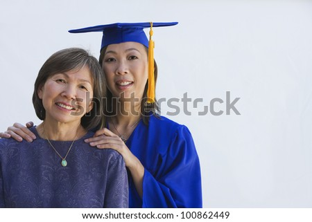 Asian woman in graduation cap and gown with mother