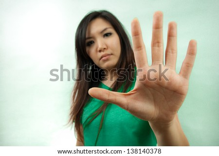 Asian woman in green set, stop sign - stock photo
