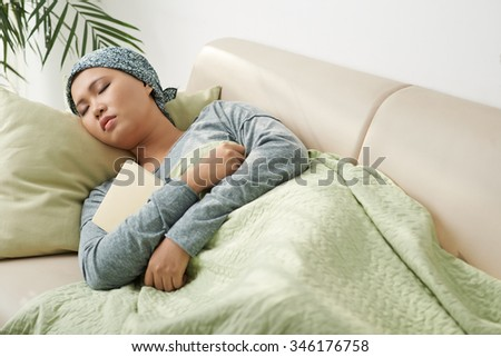 Asian woman in headscarf sleeping on the sofa with book in her hands - stock photo