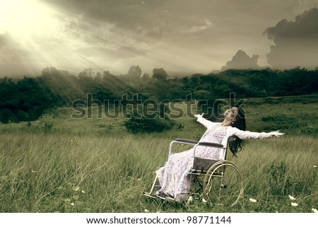 Asian woman in wheelchair embracing freedom outdoor - stock photo