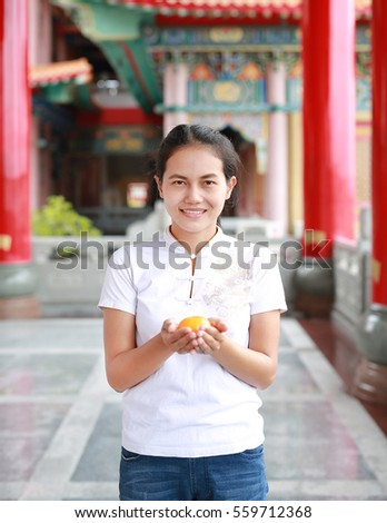 asian woman in White traditional chinese dress with holding sacred Orange at chinese temple in bangkok thailand, Chinese new year concept.