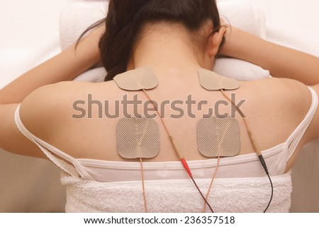 Asian woman is doing massage of electrical stimulation ( TENs ) for the back       - stock photo
