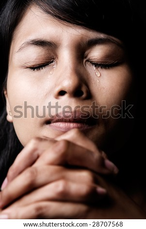 Asian woman is praying and shed tear. - stock photo