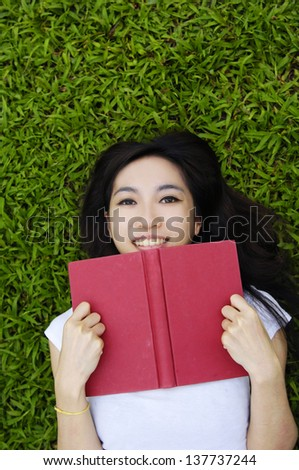 Asian woman is reading her book lying on the grass