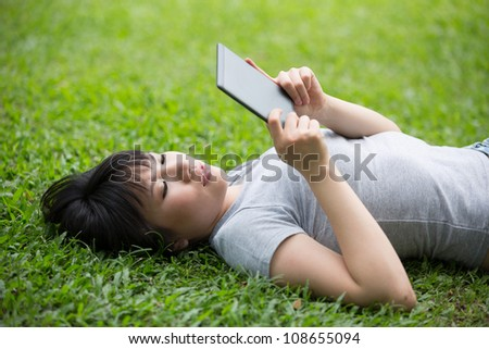 Asian woman is reading her e-book lying on the grass - stock photo