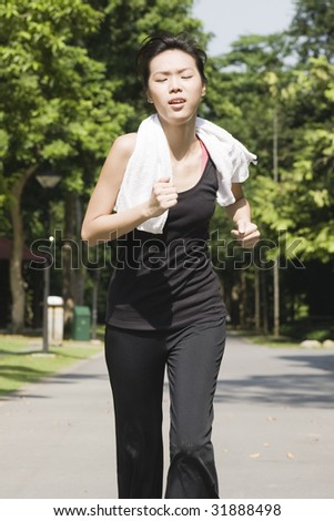 asian woman jogging alone outdoors in a park