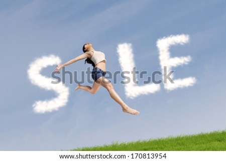 Asian woman jumping make the word 'sale'