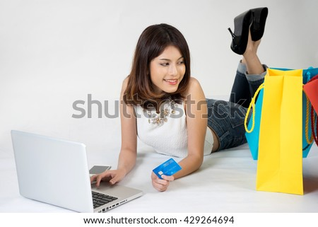 Asian woman lay down on the floor use computer and hold credit card thinking about shopping good product color yellow green red bag white background - stock photo