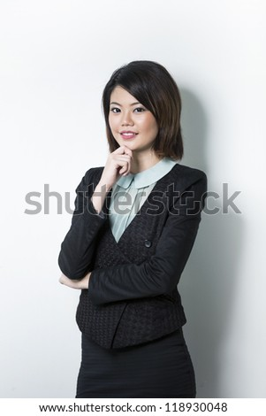 Asian Woman leaning against white wall with her hand on her chin. - stock photo