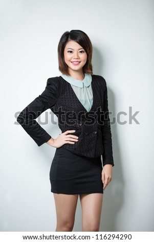 Asian Woman leaning against white wall with her hand on hip. - stock photo