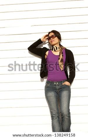 Asian woman leans against building. - stock photo