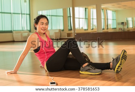 Asian woman listen music on mobile phone at gym  - female fitness relax after exercise workout break.