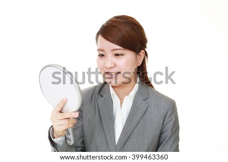 Asian woman looking at her face in mirror - stock photo
