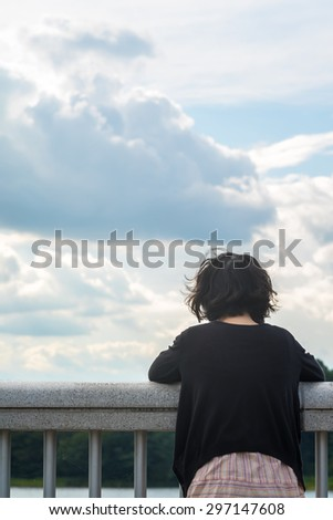Asian woman looking at sky and lake - stock photo