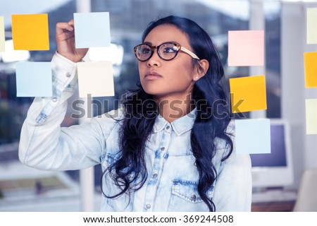 Asian woman looking at sticky notes on glass wall