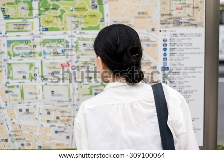 Asian woman looking doubtful about map