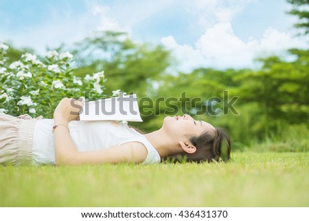 Asian woman lying grass field after she tired for reading a book in the afternoon - stock photo