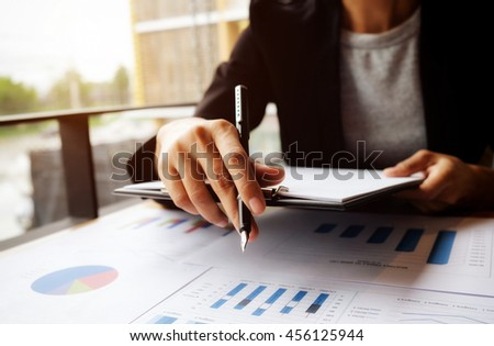 Asian woman manager putting her ideas and writing business plan at workplace, woman holding pens and papers, making notes in documents, on the table in office, vintage color, selective focus. - stock photo