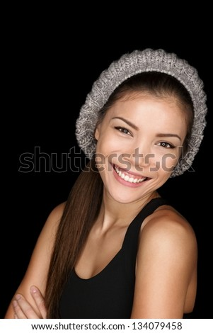 Asian woman modern hipster portrait smiling happy and confident looking at camera isolated on black background wearing knit hat. Multicultural Caucasian Asian female model in her 20s. - stock photo