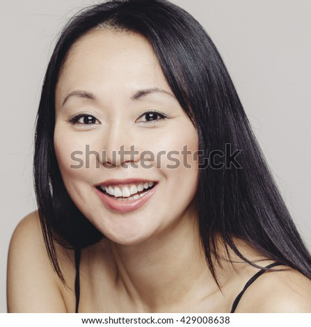 Asian woman of Japanese decent smiling with a warm grey background.