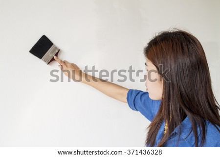 asian woman painting her wall in white