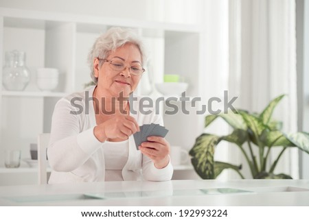 Asian woman pensioner playing cards - stock photo